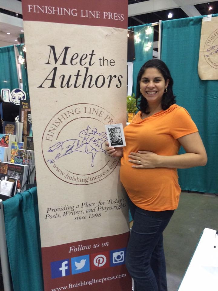 Picture of Li Yun Alvarado holding her pregnant belly and a postcard with a picture of the cover of her book Words or Water in front of a Finishing Line Press sign at AWP 2016.