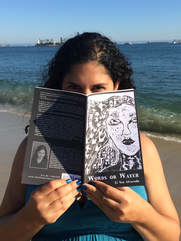 Li Yun Alvarado holding a Copy of Words or Water on the beach.